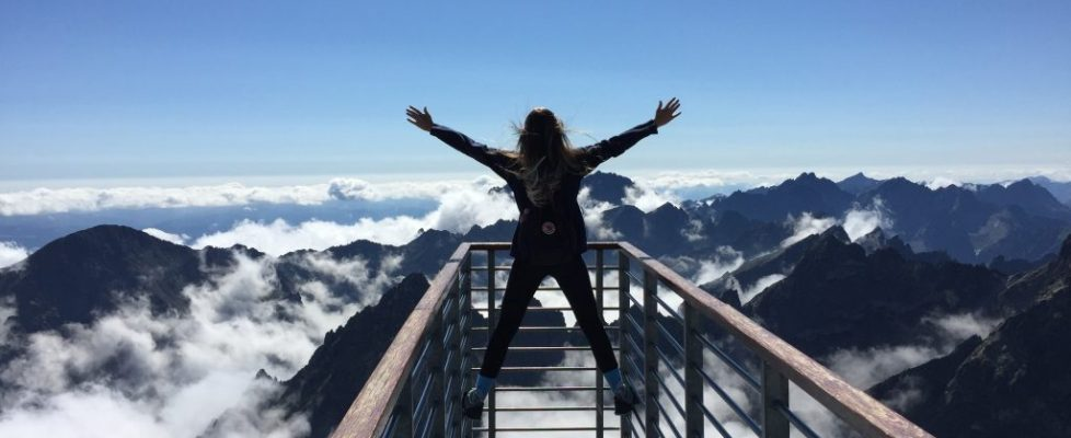 Canva - Person Standing on Hand Rails With Arms Wide Open Facing the Mountains and Clouds